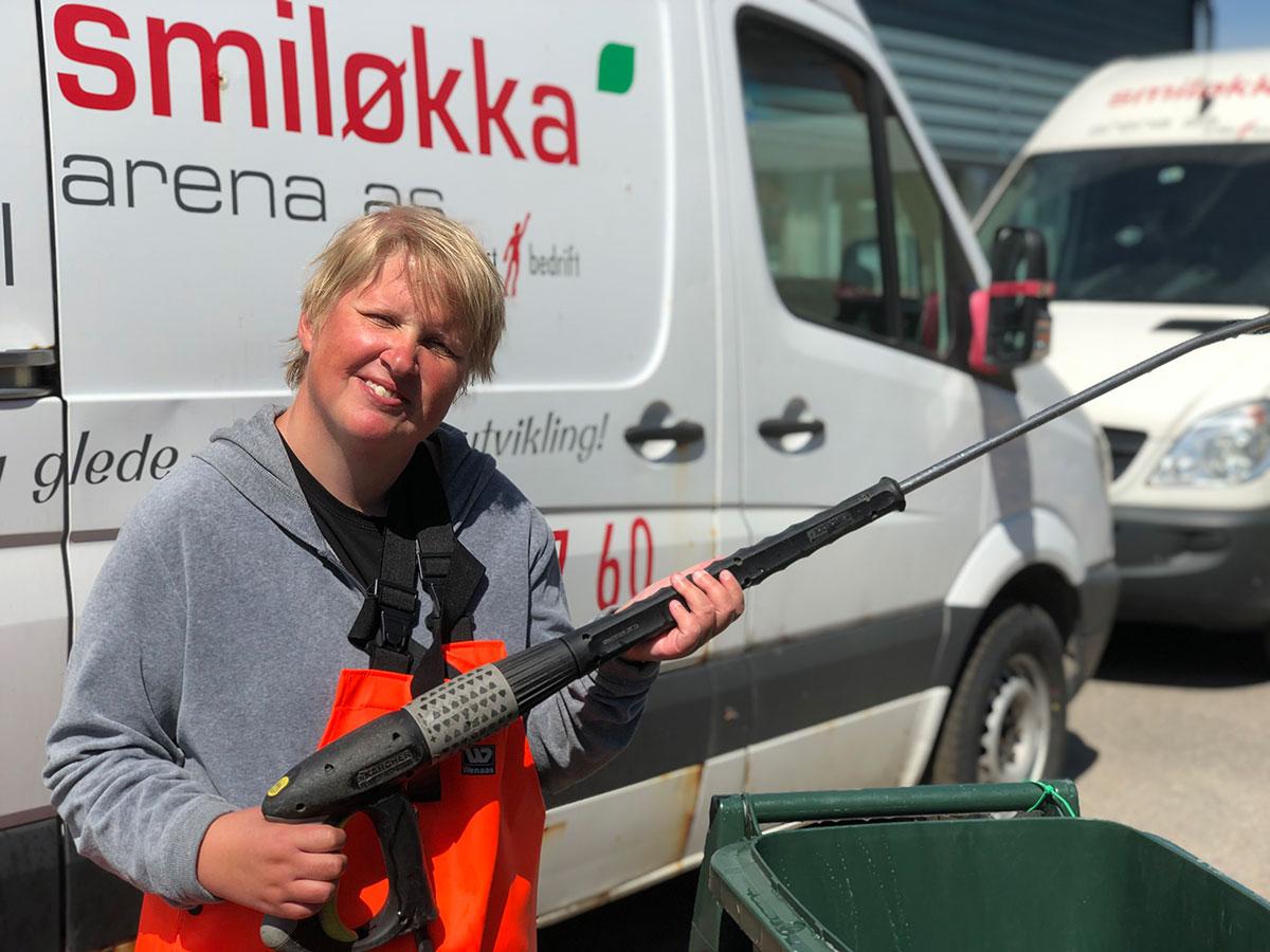 MEdarbeider hos Smiløkka vasker en dunk med et smil
